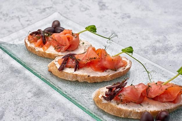 Trois bruschetta à la truite, saumon, fromage à la crème et microgreen sur une assiette en verre