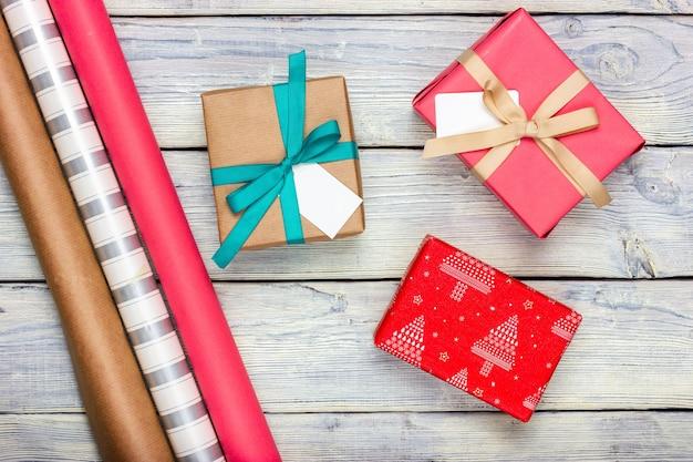 Trois cadeaux et papier d'emballage sur fond clair. vue d'en-haut.