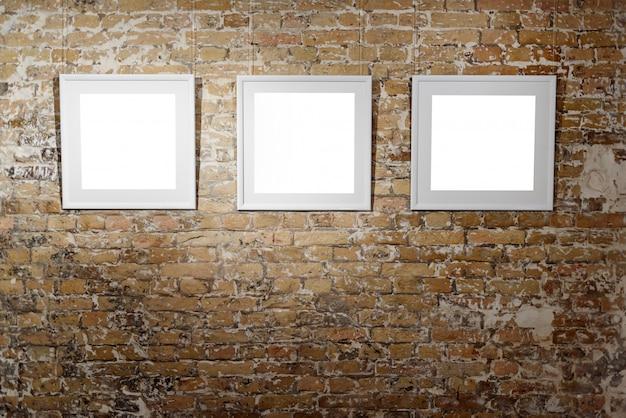 Trois cadres vides sur le mur de briques claires. affiches d'espace vide ou cadre d'art en attente d'être rempli. cadre carré noir