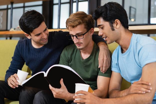 Trois camarades de classe lisent un manuel et boivent du café