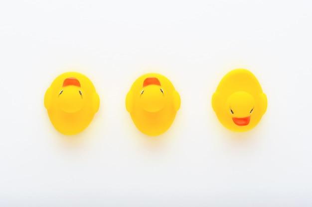 Trois canetons en caoutchouc jouet jaune sur fond blanc, concept de vues différentes