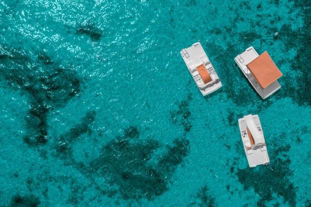 Trois catamarans à la surface de la mer bleue