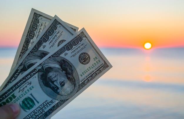 Trois cents billets d'un dollar sur fond de surface de la mer à l'aube du coucher du soleil
