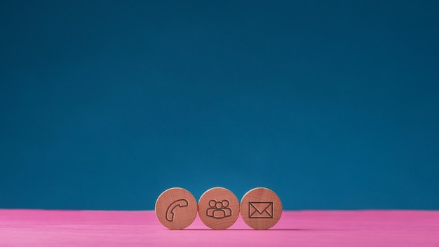 Trois cercles coupés en bois avec des icônes de contact et de communication