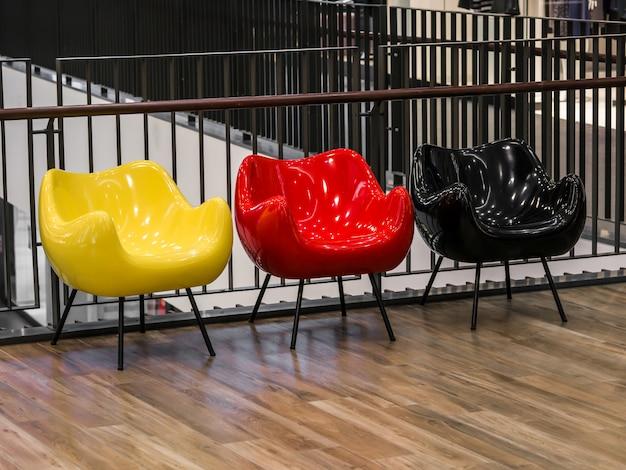 Trois chaises colorées sont dans le centre commercial