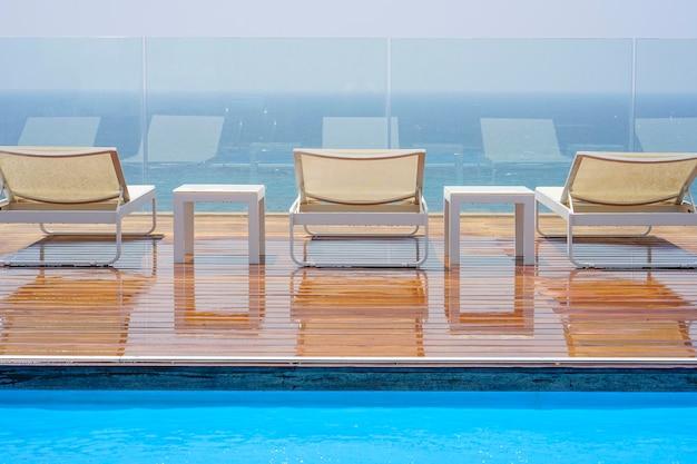 Trois chaises longues, debout et table sur un plancher en bois contre la mer