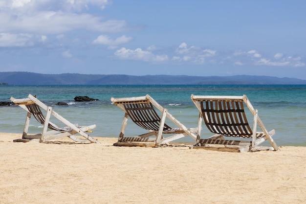 Trois chaises de plage pliantes sur la plage avec la mer et le ciel en arrière-plan à koh mak à trat