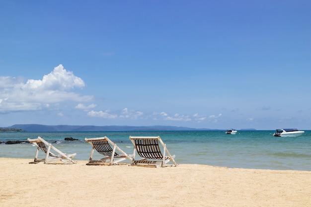 Trois chaises de plage pliantes sur la plage avec mer et ciel lumineux
