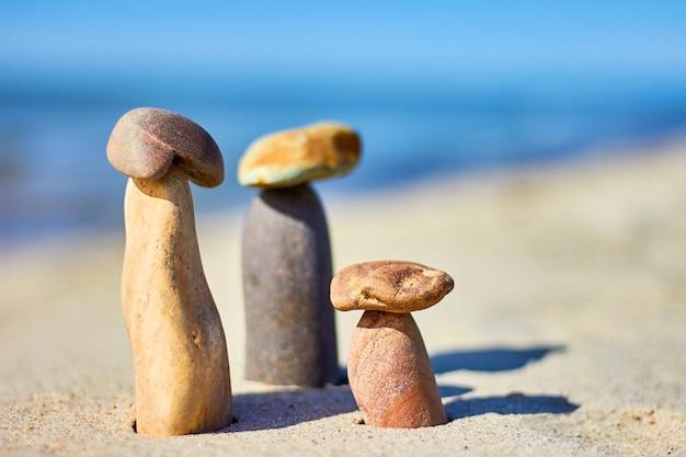 Trois champignons en pierre sur une plage de sable. équilibre des pierres