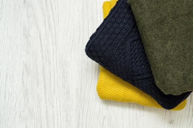 Trois chandails de couleurs chaudes sur un fond en bois