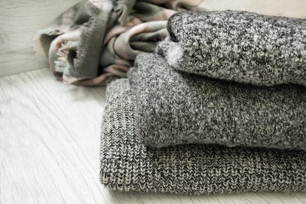Trois chandails gris sur un fond en bois