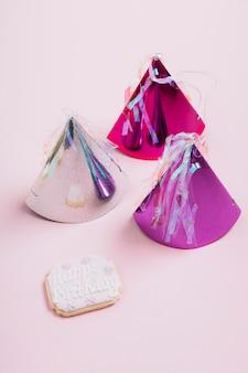 Trois chapeau de fête coloré avec biscuit de joyeux anniversaire sur fond rose