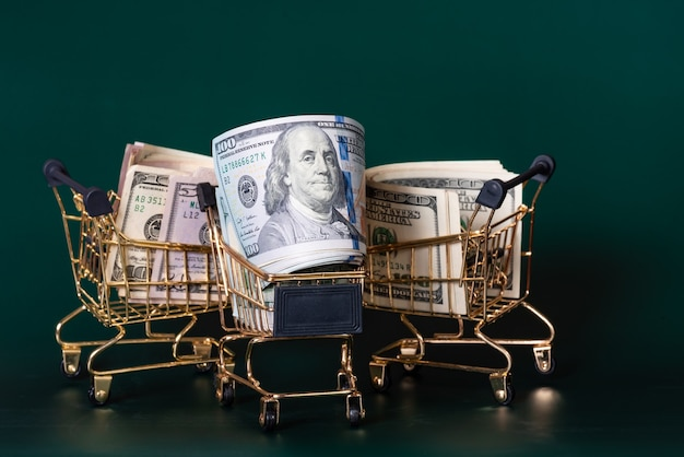 Trois chariots d'épicerie de couleur or avec des dollars sur fond vert foncé. concept bancaire et financier.