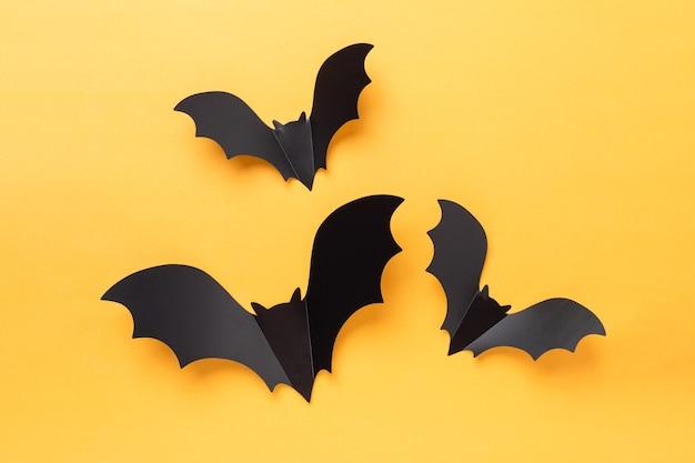 Trois chauves-souris volantes en papier noir sur fond jaune et blanc. notion d'halloween. mise à plat, espace de copie - image