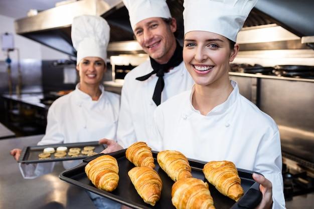 Trois chefs tenant un plateau de croissant cuit au four et des biscuits