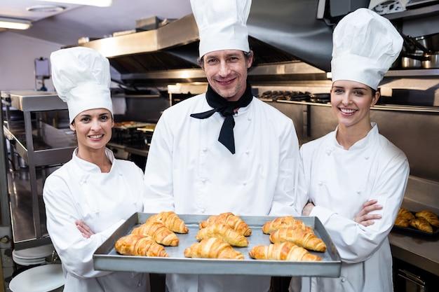 Trois chefs tenant un plateau de croissant cuit au four