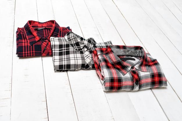 Trois chemises à carreaux sur un bois blanc. concept de vêtements.