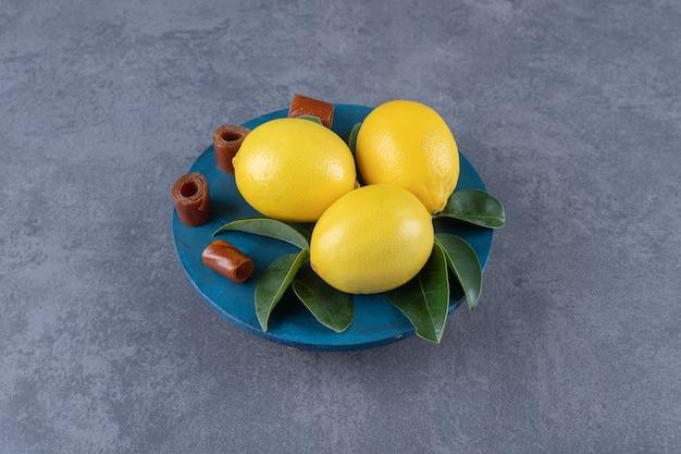 Trois citrons biologiques et feuilles sur plaque bleue.