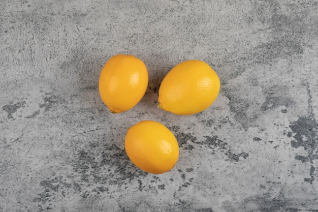 Trois citrons jaunes frais placés sur une table en pierre.