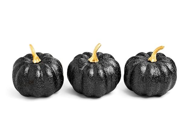 Trois citrouilles décoratives noires brillantes. décorations d'halloween. nature morte créative minimale. isolé