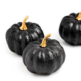 Trois citrouilles décoratives noires brillantes. nature morte créative minimale. isolé