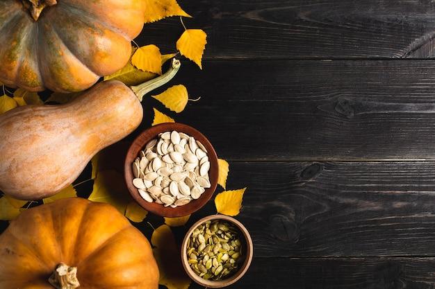 Trois citrouilles de différentes tailles sur un fond en bois noir avec des feuilles jaunes. assiette en céramique et bol en bois avec graines de citrouille. situé sur un côté. copiez l'espace. vue de dessus.