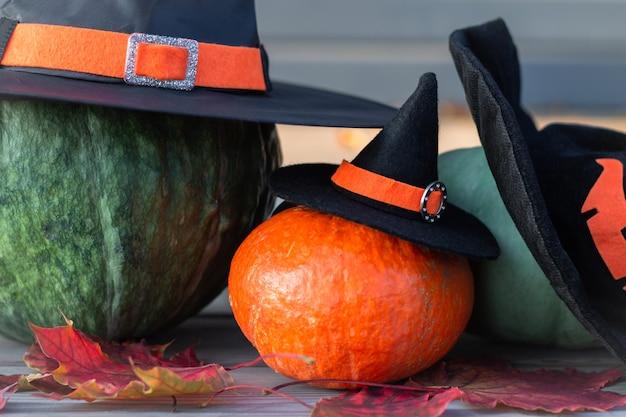 Trois citrouilles d'halloween en chapeaux de sorcière sur une terrasse en bois