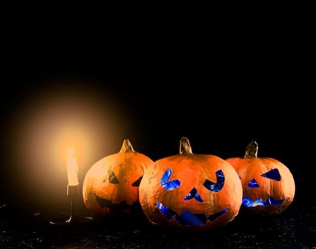 Trois citrouilles d'halloween sculptées avec un chandelier lumineux