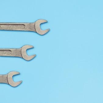 Trois clés métalliques se trouvent sur la texture du papier de couleur bleu pastel fashion