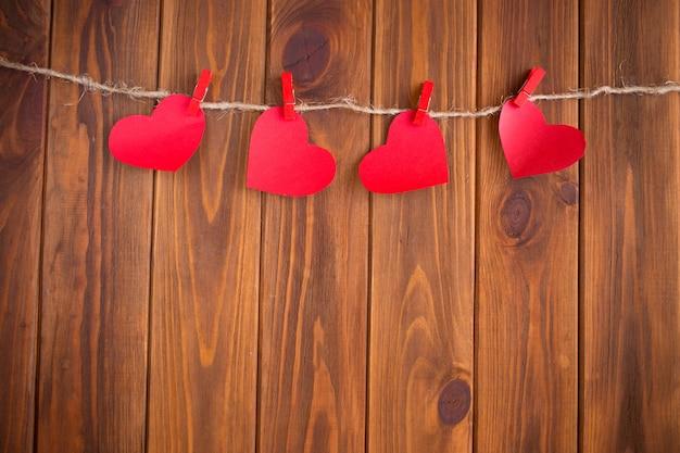Trois coeurs d'amour accroché sur fond de texture en bois, concept de carte de saint valentin