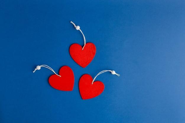 Trois coeurs rouges sur fond bleu tendance. style plat. vue de dessus