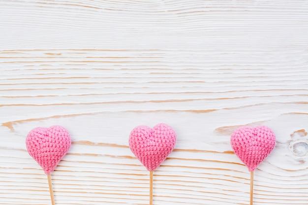 Trois coeurs tricotés roses sur un fond en bois blanc