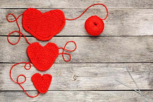 Trois coeurs tricotés rouges sur un fond en bois gris