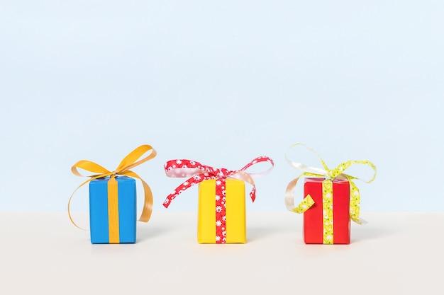 Trois coffrets cadeaux colorés sur fond pastel.