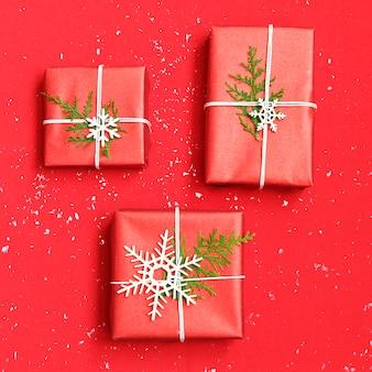 Trois coffrets cadeaux de noël décorés et flocons blancs