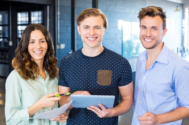 Trois collègues confiants discutant au bureau avec des documents et une tablette