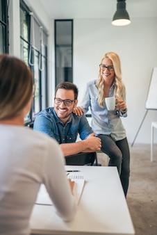 Trois collègues dans un espace de coworking ou une salle de classe moderne parlant et souriant.