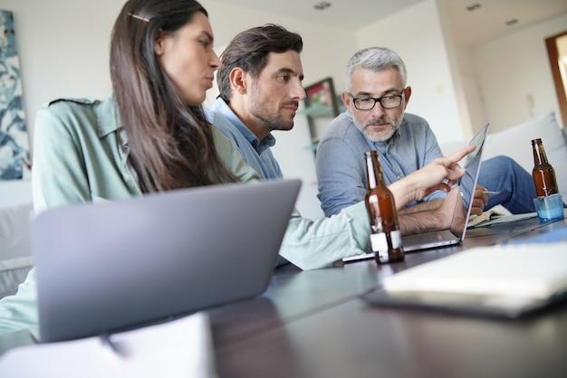 Trois collègues discutant avec des idées d'affaires à la maison