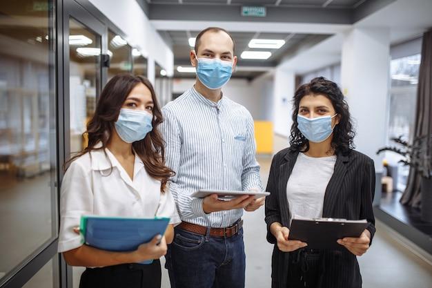 Trois collègues portant des masques médicaux discutent des affaires dans le couloir du bureau pendant la quarantaine en cas de pandémie de coronavirus.