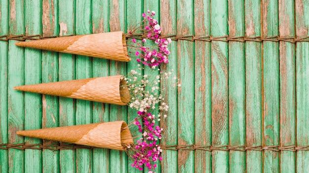 Trois cônes de gaufres avec des fleurs de bébé souffle sur fond en bois