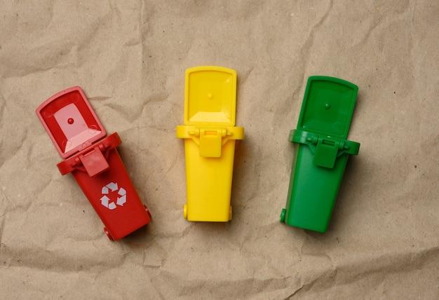 Trois contenants en plastique multicolores sur un papier brun, concept de tri correct des ordures pour un recyclage ultérieur