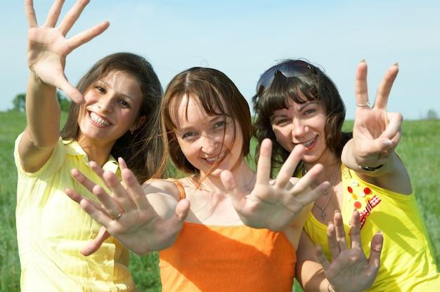 Trois copine en champ vert sous ciel bleu