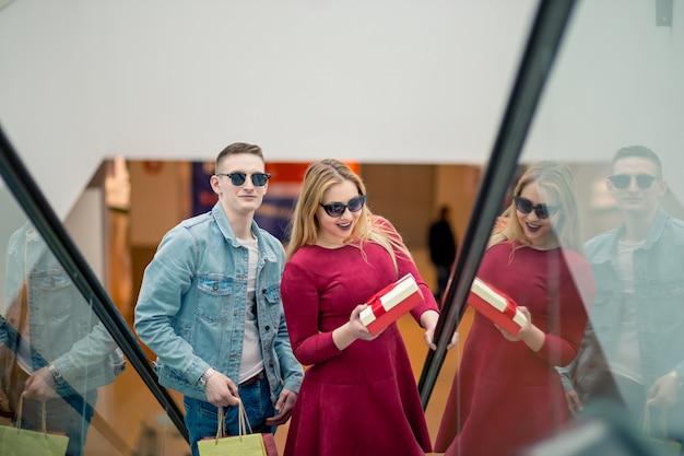 Trois copines sur l'escalator avec des sacs à provisions