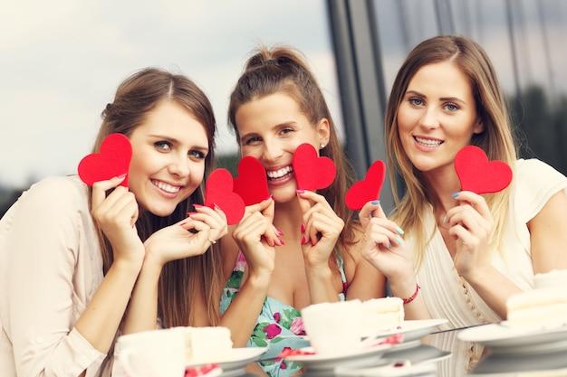 Trois copines tenant des coeurs au café