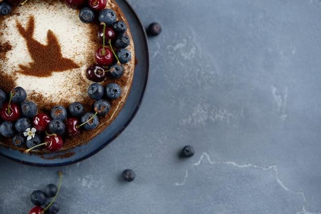 Trois couches de gâteau aux cerises avec crème sure décorées de baies et de cerises fraîches