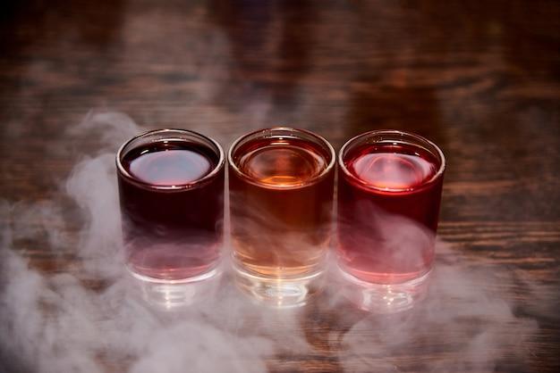 Trois coups d'alcool multicolores dans la fumée.