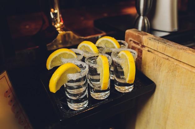 Trois coups de tequila au citron et au sel sur fond de bois.