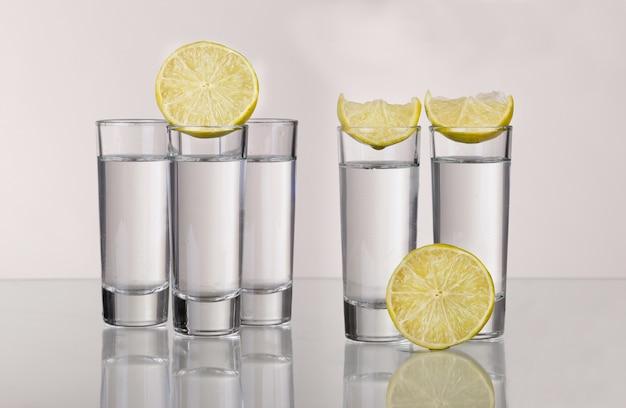 Trois coups de tequila or avec de la chaux isolé sur fond blanc