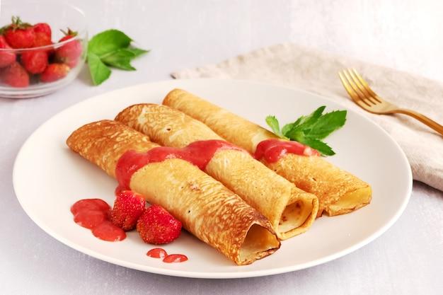 Trois crêpes recouvertes de sauce aux fraises et fraises sur une assiette