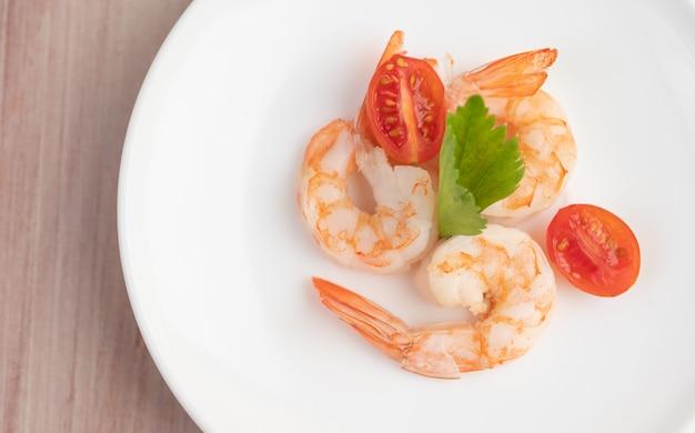 Trois crevettes fraîches et demi-tomates dans une assiette blanche sur un bois.